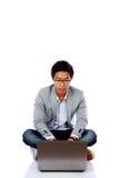 Uomo asiatico che si siede sul pavimento e che per mezzo del computer portatile Fotografia Stock Libera da Diritti