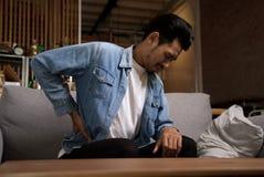 Uomo asiatico che si siede sul sofà che ha mal di schiena e che tiene il suo indietro a casa immagini stock