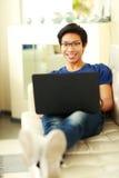 Uomo asiatico che si trova sul sofà con il computer portatile Immagine Stock Libera da Diritti