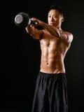 Uomo asiatico che solleva una campana del bollitore Fotografia Stock