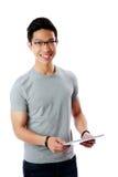 Uomo asiatico che sta con il computer della compressa Fotografie Stock Libere da Diritti