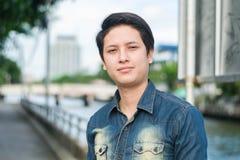 Uomo asiatico che sta e che mostra il suo fronte liscio fotografia stock libera da diritti