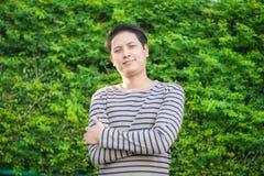 Uomo asiatico che sta e che mostra suo sorridere felice fotografia stock