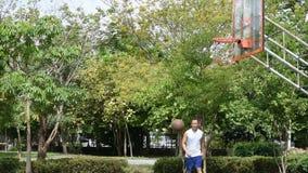 Uomo asiatico che tiene pallacanestro a disposizione e che salta tiro un albero del fondo del cerchio di pallacanestro in parco stock footage