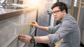 Uomo asiatico che usando misura di nastro sul contatore di cucina fotografie stock