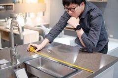 Uomo asiatico che usando misura di nastro sul contatore di cucina immagine stock libera da diritti