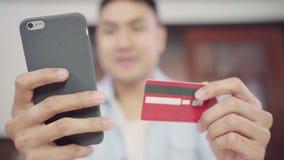 Uomo asiatico che usando smartphone per l'acquisto online e la carta di credito in Internet a casa del salone stock footage