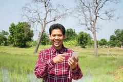 Uomo asiatico che utilizza smartphone nell'agricoltura Immagine Stock Libera da Diritti