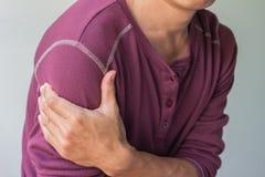 Uomo asiatico con dolore della spalla immagine stock libera da diritti