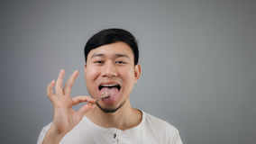 Uomo asiatico con l'osso del pollo Fotografia Stock