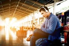 Uomo asiatico dei pantaloni a vita bassa che ascolta la musica alla stazione ferroviaria con headp Immagine Stock Libera da Diritti