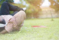 Uomo asiatico dei pantaloni a vita bassa che si trova sull'erba verde e che si rilassa per ascoltare musica dal tappo per le orec immagine stock libera da diritti