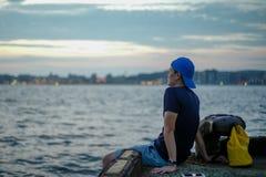Uomo asiatico del ritratto che si siede sul porto e che guarda fuori al mare con il cielo crepuscolare delle luci del bokeh e di  fotografia stock