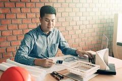 Uomo asiatico dell'architetto che lavora nel suo ufficio con la seduta e il typin Fotografia Stock