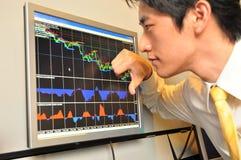 Uomo asiatico di affari che guarda il mercato azionario