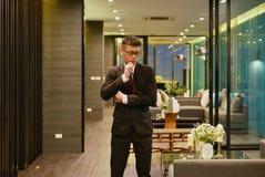 Uomo asiatico di affari che pensa nel salone di lusso nell'APAR moderno Immagini Stock