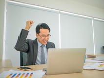 Uomo asiatico di affari che si siede molto felice immagine stock