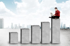 Uomo asiatico di affari che si siede sul blocchetto del grafico Fotografia Stock