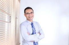 Uomo asiatico di affari di sorriso felice che sta vicino alla finestra dell'ufficio Fotografie Stock Libere da Diritti
