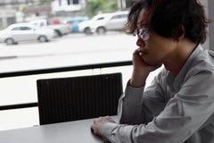 Uomo asiatico disoccupato di ribaltamento nella depressione che si siede nella casa immagini stock libere da diritti