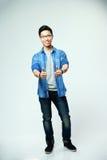 Uomo asiatico felice che mostra i pollici su Fotografia Stock