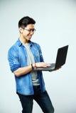 Uomo asiatico felice che per mezzo del computer portatile Immagine Stock Libera da Diritti