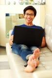 Uomo asiatico felice che si trova sul sofà con il computer portatile Fotografia Stock