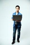 Uomo asiatico felice che sta con il computer portatile Immagine Stock Libera da Diritti