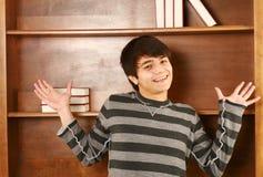 Uomo asiatico felice davanti alla mensola di libro Fotografie Stock