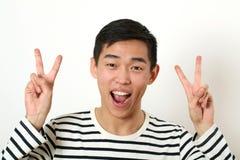 Uomo asiatico giovane di risata che dà due segni di vittoria e che esamina Fotografia Stock Libera da Diritti