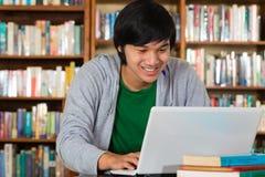 Uomo asiatico in libreria con il computer portatile Fotografia Stock