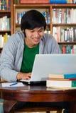 Uomo asiatico in libreria con il computer portatile Immagini Stock Libere da Diritti