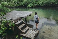 Uomo asiatico nel bello tempo di vacanza della laguna della foresta della mangrovia immagini stock