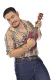 Uomo asiatico in plaid che gioca ukulele Fotografie Stock