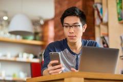 Uomo asiatico premuroso che per mezzo dello smartphone e del computer portatile Fotografie Stock Libere da Diritti