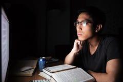 Uomo asiatico serio che studia con i libri ed il computer Fotografie Stock
