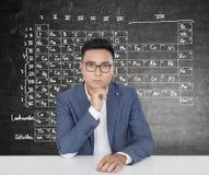 Uomo asiatico serio e una tavola periodica Fotografie Stock