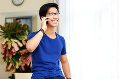 Uomo asiatico sorridente che parla sul telefono Immagine Stock