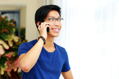 Uomo asiatico sorridente che parla sul telefono Fotografia Stock Libera da Diritti