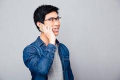 Uomo asiatico sorridente che parla sul telefono Immagini Stock