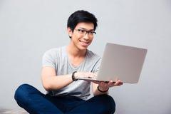 Uomo asiatico sorridente che per mezzo del computer portatile Fotografia Stock