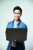 Uomo asiatico sorridente che sta con il computer portatile Fotografia Stock