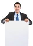 Uomo asiatico sorridente di affari che tiene bordo vuoto fotografie stock libere da diritti