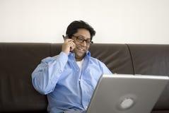Uomo asiatico sul telefono con il computer portatile Immagini Stock Libere da Diritti