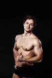 Uomo atletico bello che mostra pollice-su in pantaloni neri La forte BO Fotografia Stock Libera da Diritti
