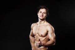 Uomo atletico bello che mostra pollice-su in pantaloni neri La forte BO Immagini Stock