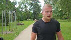 Uomo atletico bello prima di correre nel parco stock footage