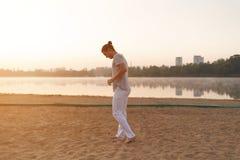 Uomo atletico casuale che si prepara per l'allenamento sulla spiaggia Immagini Stock Libere da Diritti