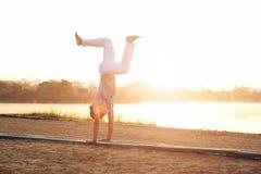 Uomo atletico casuale in pantaloni bianchi sottosopra sulla spiaggia Immagine Stock