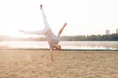 Uomo atletico casuale sulla spiaggia mentre allenamento Fotografia Stock
